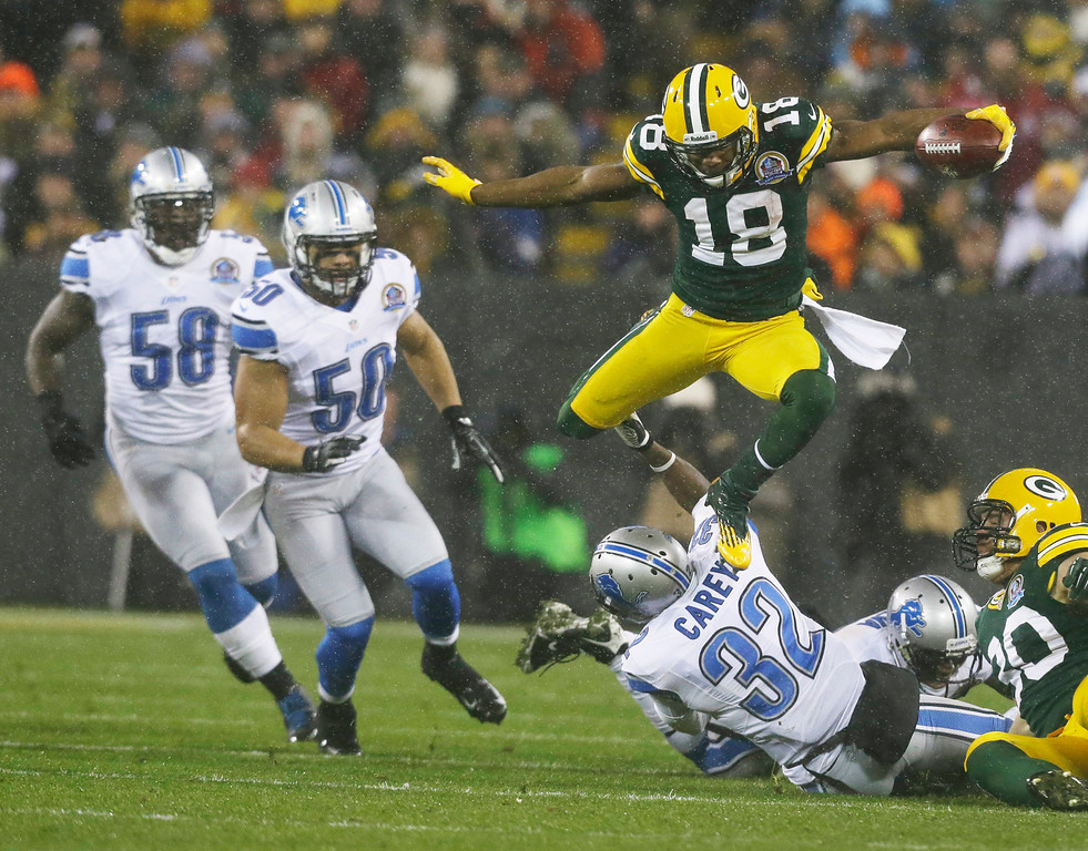 Description of . Green Bay Packers' Randall Cobb leaps over Detroit Lions' Don Carey (32) as he runs back a kick during the first half of an NFL football game Sunday, Dec. 9, 2012, in Green Bay, Wis. (AP Photo/Jeffrey Phelps)