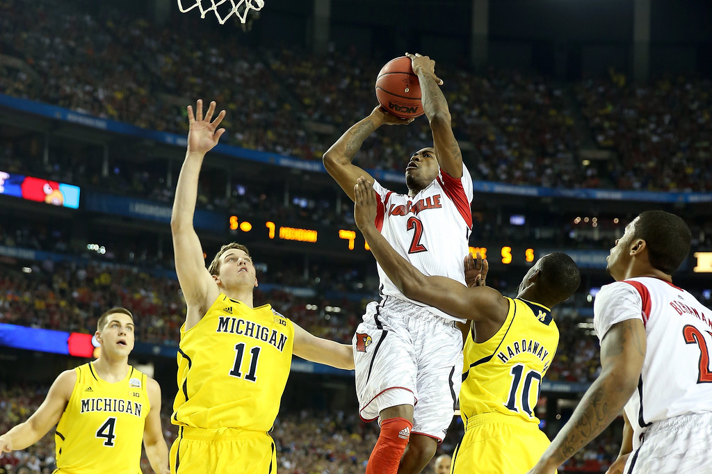 Description of . Russ Smith #2 of the Louisville Cardinals drives for a shot attempt in the first half against Nik Stauskas #11 and Tim Hardaway Jr. #10 of the Michigan Wolverines during the 2013 NCAA Men's Final Four Championship at the Georgia Dome on April 8, 2013 in Atlanta, Georgia.  (Photo by Andy Lyons/Getty Images)