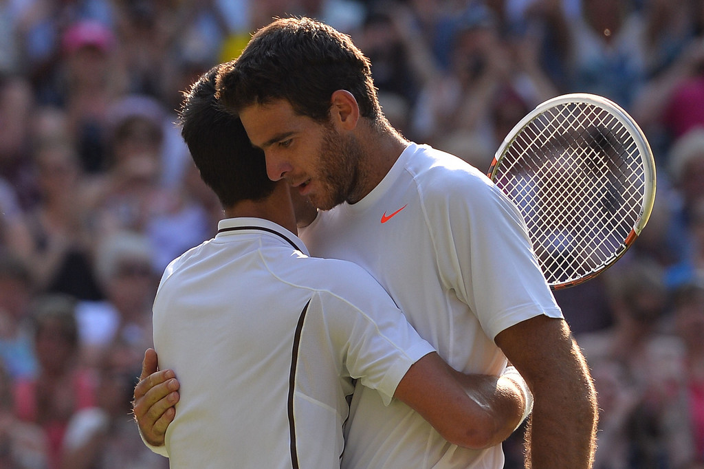 Description of . Serbia\'s Novak Djokovic (L) embraces Argentina\'s Juan Martin Del Potro (R) after Djokovic\'s victory in their men\'s singles semi-final match on day eleven of the 2013 Wimbledon Championships tennis tournament at the All England Club in Wimbledon, southwest London, on July 5, 2013. Djokovic won 7-5, 4-6, 7-6, 6-7, 6-3. CARL COURT/AFP/Getty Images