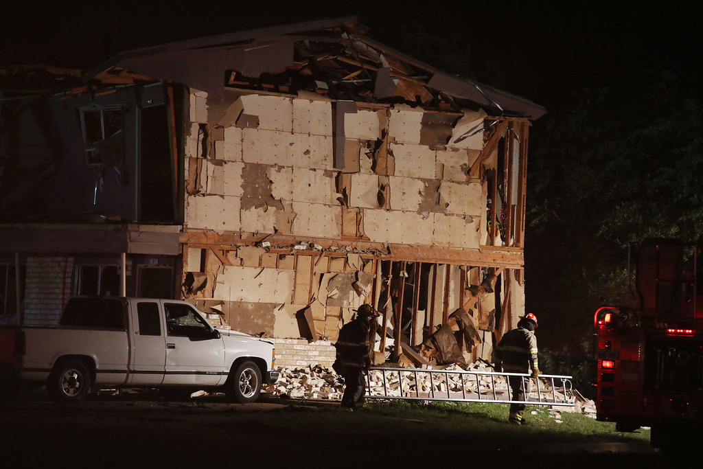 Description of . Rescue workers pass a damaged apartment complex after a nearby fertilizer plant exploded Wednesday, April 17, 2013, in West, Texas. (AP Photo/ Waco Tribune Herald, Rod Aydelotte)