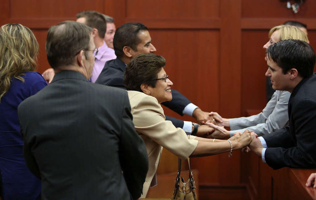 Description of . George Zimmerman's family celebrates with their legal team after the jury found him not guilty in the 2012 shooting death of Trayvon Martin at the Seminole County Criminal Justice Center in Sanford, Florida, July 13, 2013. Zimmerman was acquitted of all charges on Saturday for the fatal shooting of unarmed black teenager Trayvon Martin in this central Florida town in February of last year.  REUTERS/Gary W. Green/Pool