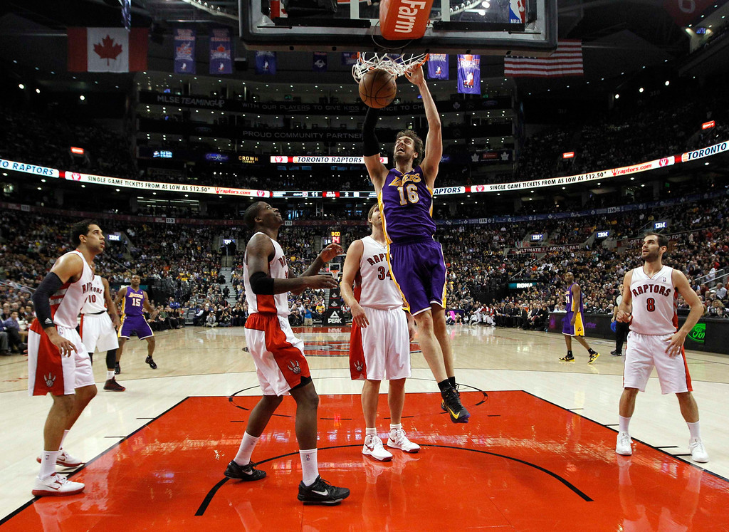 Description of . Los Angeles Lakers' Pau Gasol (C) goes up for a slam dunk past the Toronto Raptors during the first half of their NBA basketball game in Toronto, January 20, 2013.  REUTERS/Mark Blinch