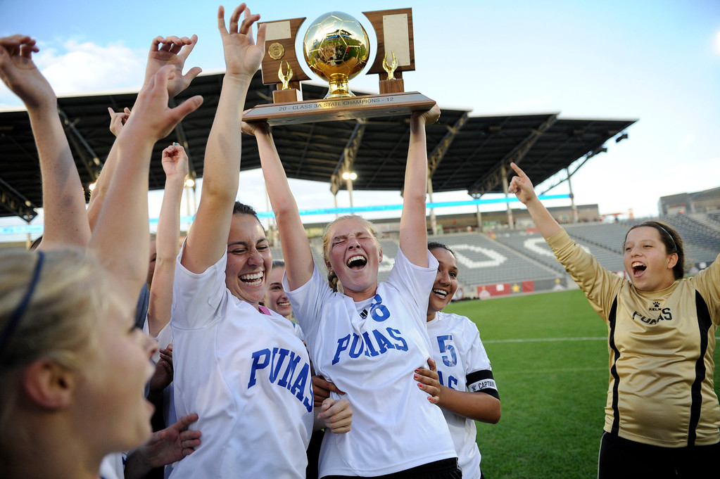Description of . Peak to Peak Carissa Thomas (6) Alex Johnson (8) and Lauren Jones (5) celebrate with the trophy after their win over Colorado Academy to capture the 3A State Girls Soccer Championship Tuesday, May 22, 2012 at Dick's Sporting Goods Park. John Leyba, The Denver Post