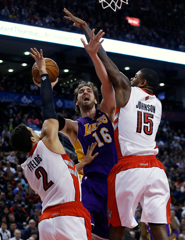 Description of . Los Angeles Lakers' Pau Gasol (C) goes to the basket against Toronto Raptors' Landry Fields (L) and Amir Johnson (R) during the second half of their NBA basketball game in Toronto, January 20, 2013.     REUTERS/Mark Blinch