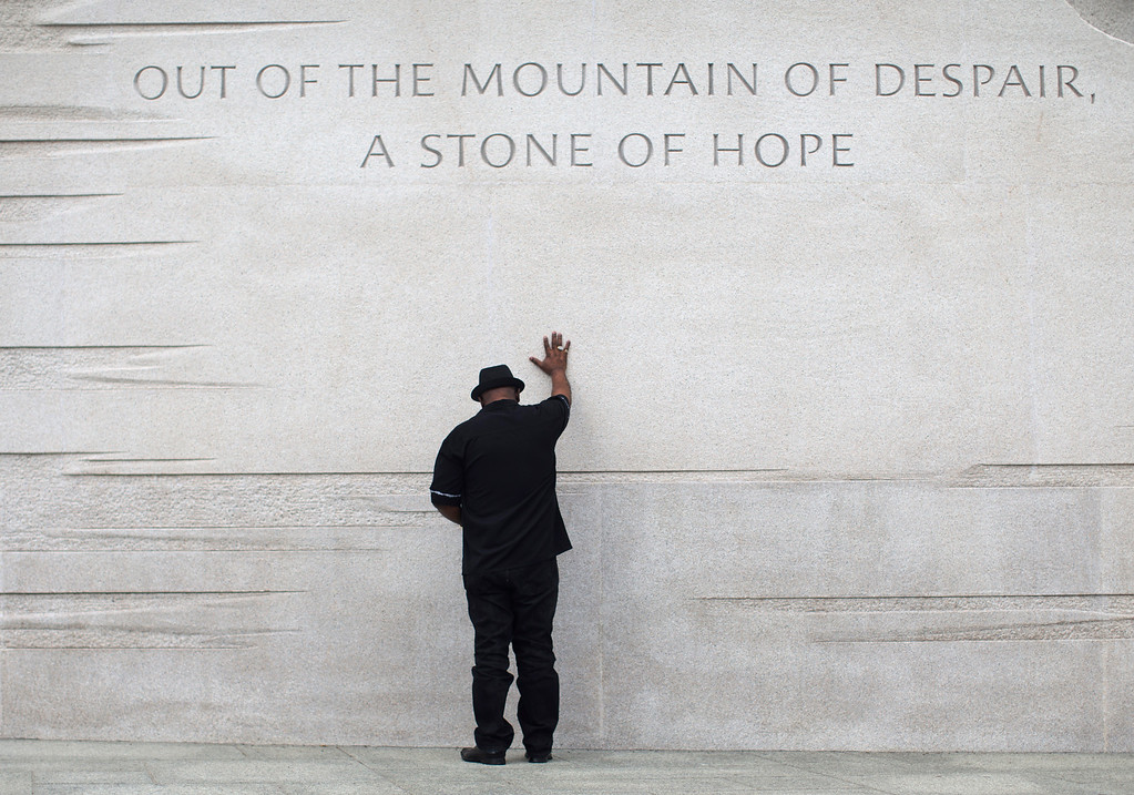Description of . Rev. Bobby Turner or Columbus, Ohio, places his hand on the Martin Luther King Jr. Memorial, Thursday, Aug. 22, 2013, in Washington.  (AP Photo/Carolyn Kaster, File)