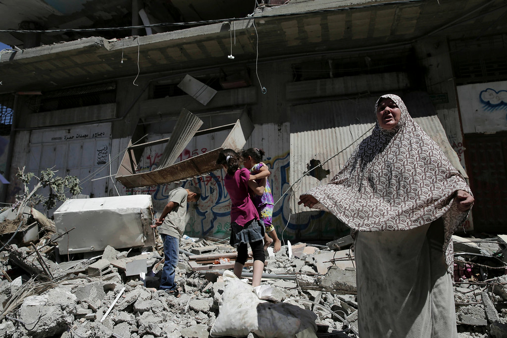 Description of . A Palestinian woman stands in front of a damaged apartment building of the al-Yazje family, which was hit by an overnight Israeli missile in Gaza City on Thursday, July 17, 2014. The Israeli military said it has struck 37 targets in Gaza ahead of a five-hour humanitarian cease-fire meant to allow civilians to stock up after 10 days of fighting. (AP Photo/Adel Hana)