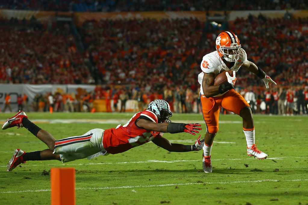 Description of . MIAMI GARDENS, FL - JANUARY 03: Roderick McDowell #25 of the Clemson Tigers runs past Tyvis Powell #23 of the Ohio State Buckeyes in the second quarter during the Discover Orange Bowl at Sun Life Stadium on January 3, 2014 in Miami Gardens, Florida.  (Photo by Streeter Lecka/Getty Images)