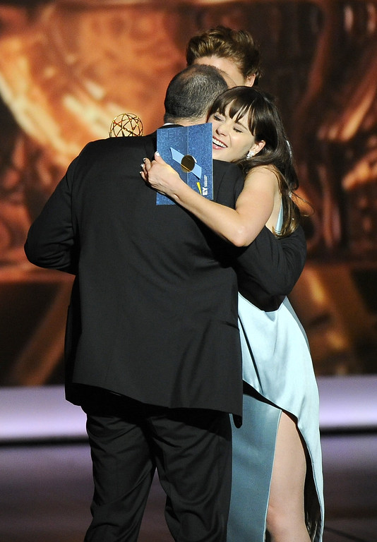 Description of . Zooey Deschanel embraces Tony Hale, left, after he received the award for outstanding supporting actor in a comedy series to Tony Hale on stage at the 65th Primetime Emmy Awards at Nokia Theatre on Sunday Sept. 22, 2013, in Los Angeles.  (Photo by Chris Pizzello/Invision/AP)