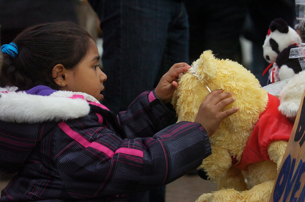 Description of . A young girl fixed a tiara on a teddy bear at the memorial that was set up in the center of Sandy Hook after a fatal shooting killed 20 children and 6 adults at the Sandy Hook Elementary on Friday the 14th.Photo Erica Miller 12/18/12 Memorial