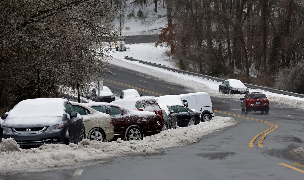 Description of . Abandoned vehicles line a roadside following a snow and ice storm in Chapel Hill, N.C., Thursday, Feb. 13, 2014. The National Weather Service issued a winter storm warning lasting into Thursday covering 95 of the state\'s 100 counties. (AP Photo/Gerry Broome)