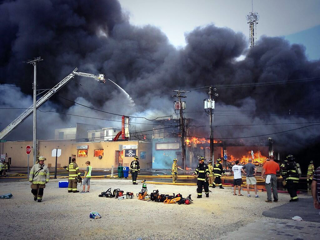 Description of . Firefighters battle a raging fire on the boardwalk in Seaside Heights, N.J. that apparently started in an ice cream shop and has spread several blocks to neighboring Seaside Heights, Thursday, Sept. 12, 2013. The boardwalk was damaged in Superstorm Sandy and was being repaired. (AP Photo/The Asbury Park Press, Kristi Funderburk)