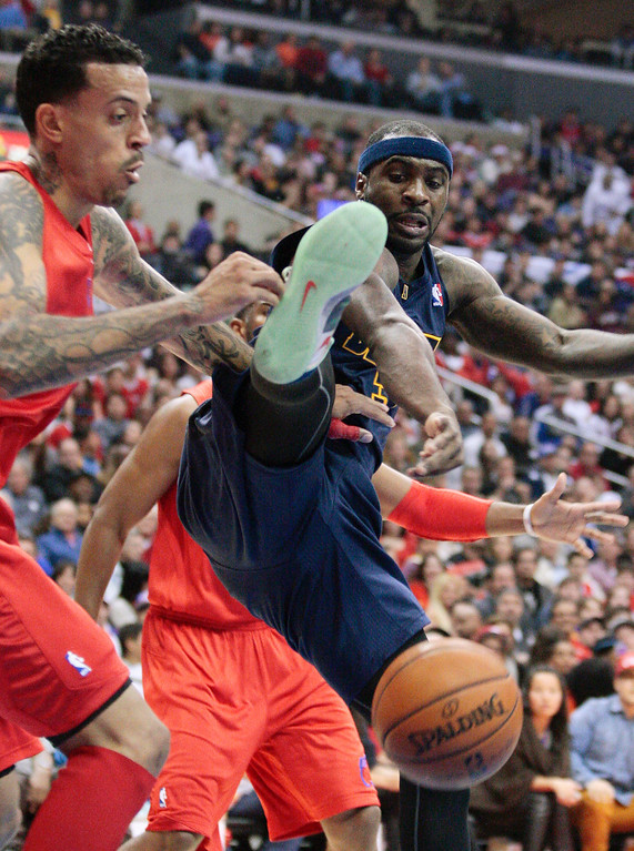 Description of . Denver Nuggets guard Ty Lawson, right, is fouled by Los Angeles Clippers' Matt Barnes, left, as he drives to the basket in the first half of their NBA basketball game, Tuesday, Dec. 25, 2012, in Los Angeles. (AP Photo/Jason Redmond)