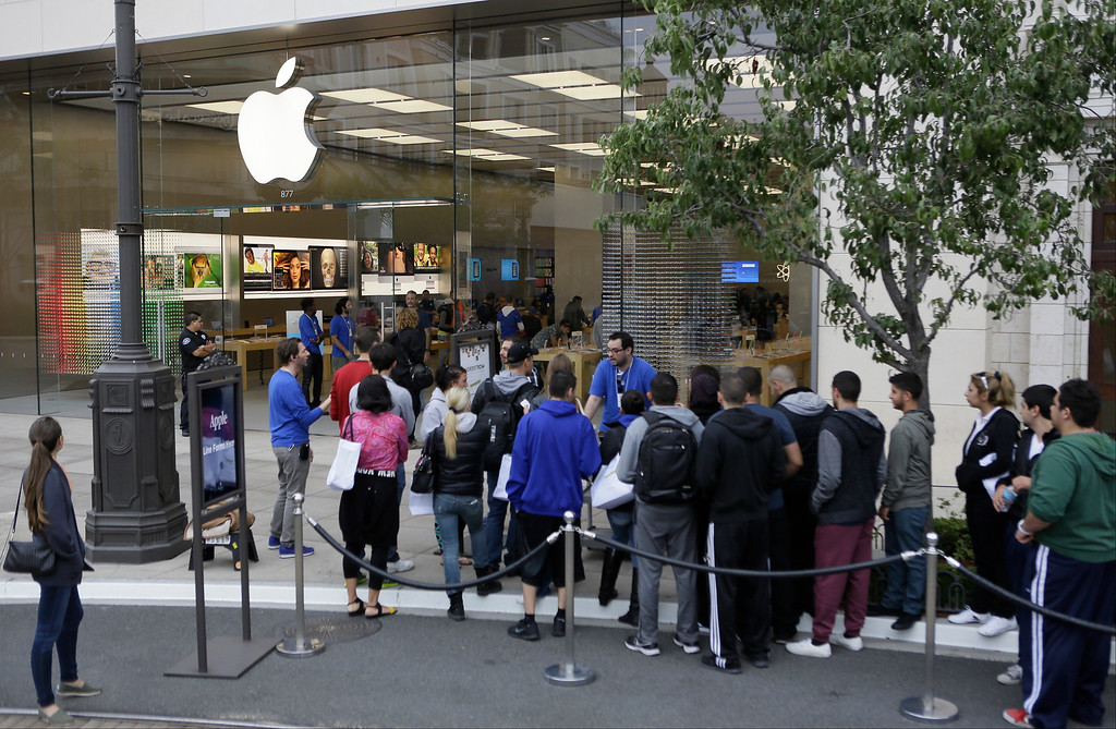 Description of . Customers wait in line to buy the latest versions of the iPhone during the opening day of sales of the iPhone 5s and iPhone 5C at the Apple store at the Americana at Brand mall in Glendale, Calif., Friday, Sept. 20, 2013. (AP Photo/Damian Dovarganes)