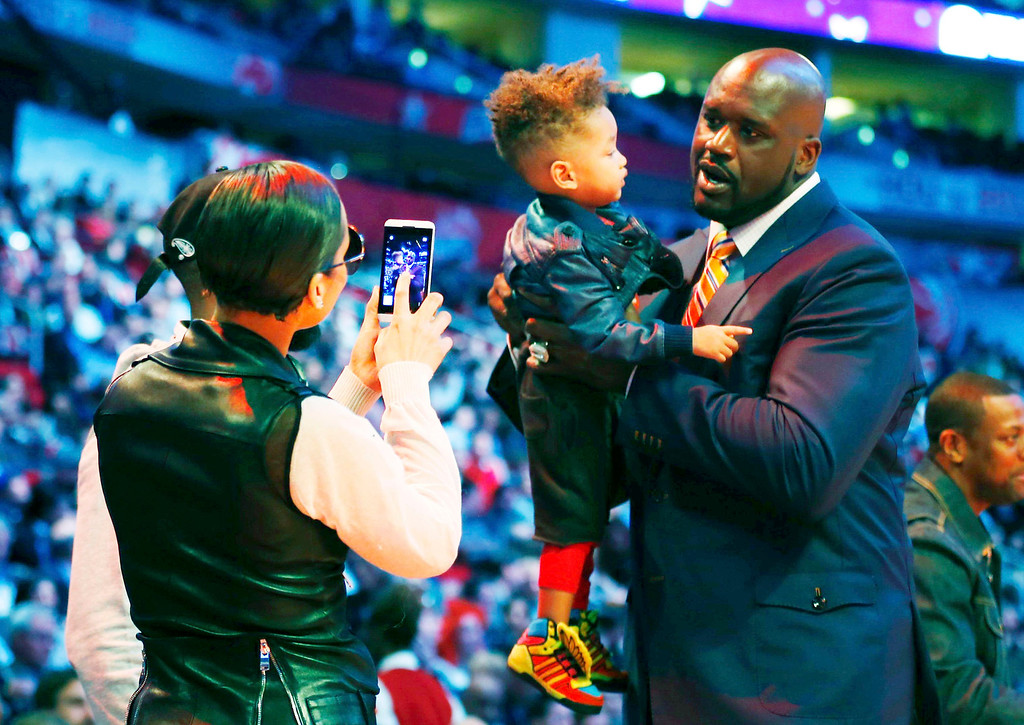Description of . Singer Alicia Keys (L) takes a picture of her son Egypt Daoud Dean with NBA legend Shaquille O'Neal during the NBA basketball All-Star weekend in Houston, Texas, February 16, 2013.  REUTERS/Jeff Haynes
