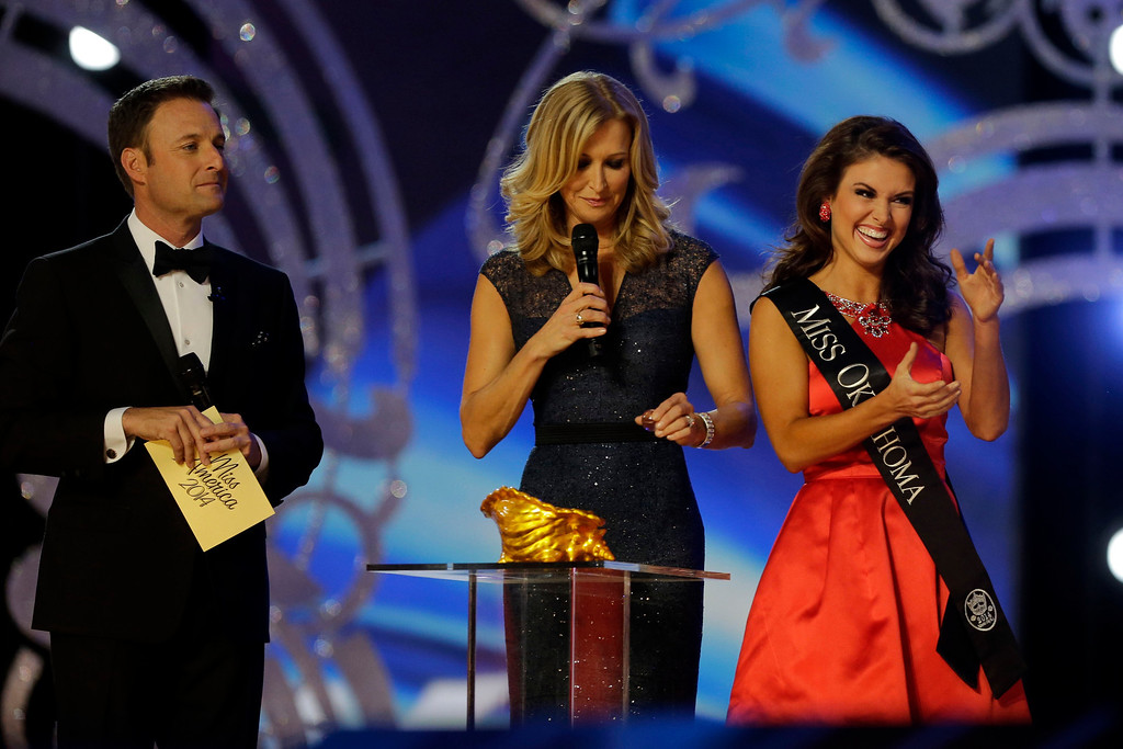 Description of . Miss Oklahoma Kelsey Griswold, right, reacts before answering a question during the Miss America 2014 pageant, Sunday, Sept. 15, 2013, in Atlantic City, N.J. (AP Photo/Mel Evans)
