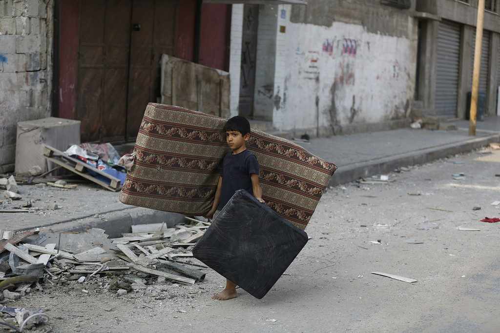 Description of . A Palestinian boy carries a mattress and a cushion he recovered from his family's damaged apartment as he walks amid debris on a deserted street in the centre of Gaza City on July 22, 2014. A series of Israeli air strikes early in the morning killed seven people in Gaza, including five members of the same family, emergency services spokesman Ashraf al-Qudra said. AFP PHOTO / MOHAMMED ABED/AFP/Getty Images