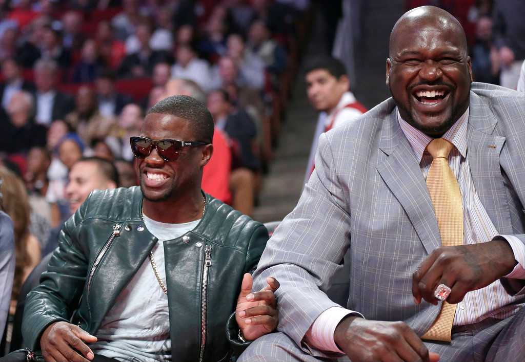 Description of . Kevin Hart, left, laughs with Shaquille O'Neal during the first half of the NBA All-Star basketball game Sunday, Feb. 17, 2013, in Houston. (AP Photo/Eric Gay)