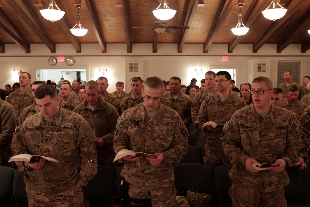 Description of . US soldiers and service members with the NATO- led International Security Assistance Force (ISAF) attend a religious ceremony on Christmas Eve at Bagram military base in Kabul, Afghanistan, Tuesday Dec. 24, 2013. The commander of NATO forces in eastern Afghanistan spent Christmas Eve visiting U.S. troops at bases across the mountainous region to bring them holiday greetings and gifts for a few lucky soldiers. (AP Photo/Rahmat Gul)