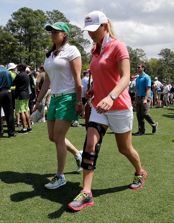. Skier Lindsey Vonn and her physical therapist Lindsay Winninger walk through the Augusta National golf course with her leg brace while following Tiger Woods during the second round of the Masters golf tournament Friday, April 12, 2013, in Augusta, Ga. (AP Photo/David J. Phillip)