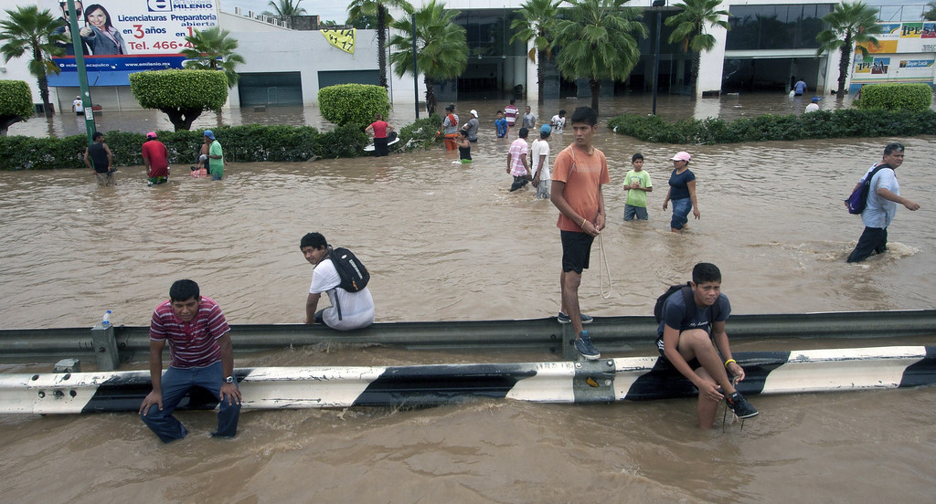 Description of . Residents wade through a flooded street in Acapulco, Guerrero state, Mexico, on September 17, 2013 as heavy rains hit the country. Mexican authorities scrambled Tuesday to launch an air lift to evacuate tens of thousands of tourists stranded amid floods in the resort of Acapulco following a pair of deadly storms. The official death toll rose to 47 after the tropical storms, Ingrid and Manuel, swarmed large swaths of the country during a three-day holiday weekend, sparking landslides and causing rivers to overflow in several states. Pedro PARDO/AFP/Getty Images