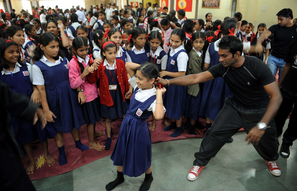 Description of . An Indian instructor (2R) shows a self defense technique to a school girl during classes at a school in Mumbai on January 4, 2013. After nearly three weeks of lurid reporting on a horrifying gang-rape in New Delhi, women in the Indian capital said they were more anxious than ever, leading to a surge in interest in self-defense classes.   PUNIT PARANJPE/AFP/Getty Images