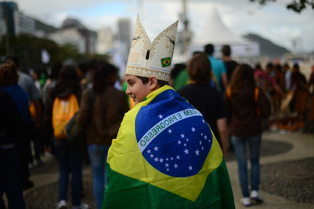 Description of . A boy wrapped in a Brazilian flag heads to Copacabana beach to wait for the arrival of the pontiff who will participate in a re-enactment of the 14 Stations of the Cross -- scenes of Jesus carrying the cross to his crucifixion -- in Rio de Janeiro, on July 26, 2013. Pope Francis, who is in Rio for the weeklong gathering of young Catholics World Youth Day, took his high-octane mission to