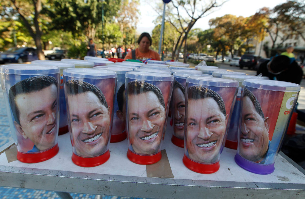 Description of . Souvenir mugs of Venezuela's late President Hugo Chavez are offered for sale as thousands waited to view his body in state, at the military academy in Caracas March 8, 2013.     REUTERS/Mariana Bazo