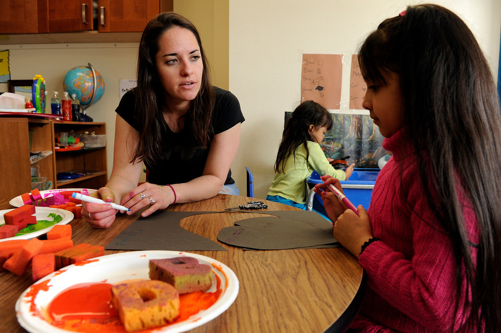 Description of . DENVER, CO - APRIL 3: Kate Murphy helps her student, Emily A., 5, to make a card for her uncle during class at the Children's Outreach Project on April 3, 2014, in Denver, Colorado. The school is a nonprofit that provides therapy, education and daycare to children between 2-6 years old who have developmental delays like moderate Down syndrome and speech impediments. (Photo by Anya Semenoff/The Denver Post)