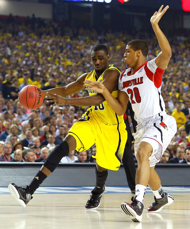 Description of . Michigan Wolverines guard Tim Hardaway Jr. (L) drives to the net on Louisville Cardinals guard/forward Wayne Blackshear during the first half of their NCAA men's Final Four championship basketball game in Atlanta, Georgia April 8, 2013. REUTERS/Chris Keane
