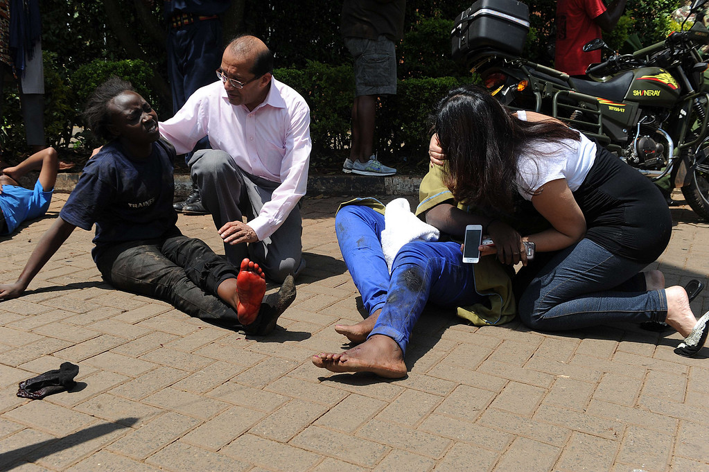 Description of . Injured people receive assistance from by passers after masked gunmen stormed an upmarket mall and sprayed gunfire on shoppers and staff, killing at least thirteen on September 21, 2013 in Nairobi.  AFP PHOTO/SIMON MAINA/AFP/Getty Images