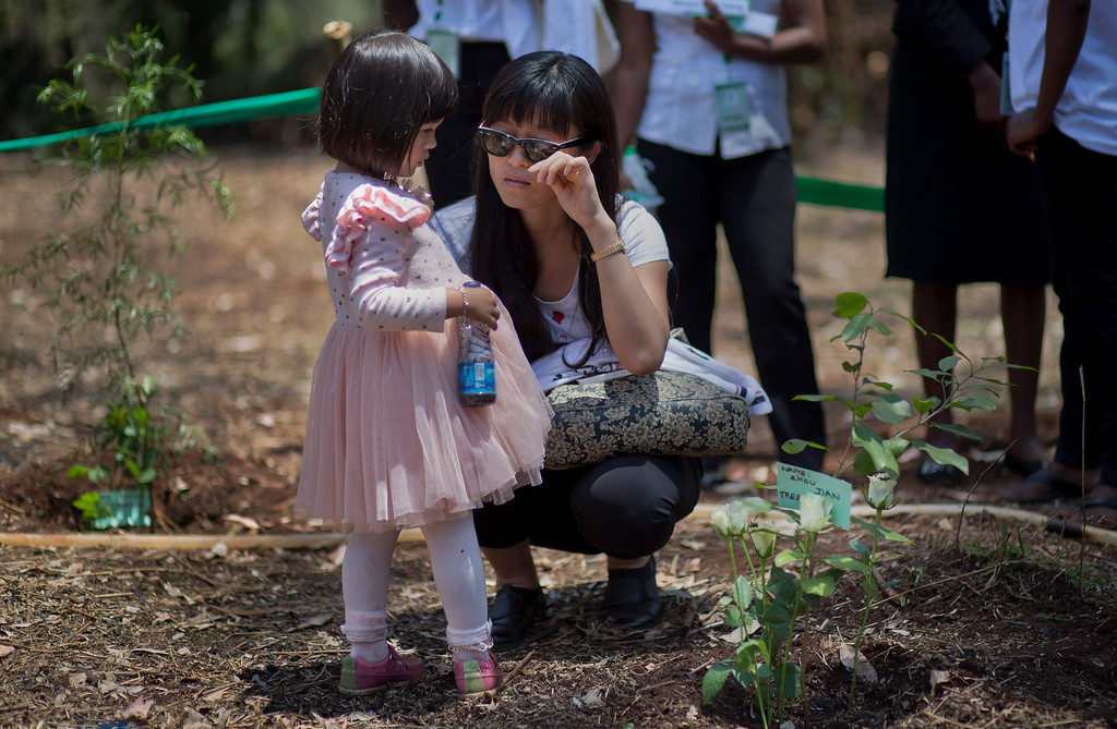 Description of . Wendy Zhang and her daughter Stella, 3, crouch down by the tree she planted in memory of her sister-in-law Zhou Jian who died in the attack, at a memorial service marking the one-month anniversary of the Sept. 21 Westgate Mall terrorist attack, in Karura Forest in Nairobi, Kenya Monday, Oct. 21, 2013. Families and friends of those killed in the attack planted trees in memory of lost loved ones in a ceremony that stressed that the attack occurred against people of all races and religions. (AP Photo/Ben Curtis)