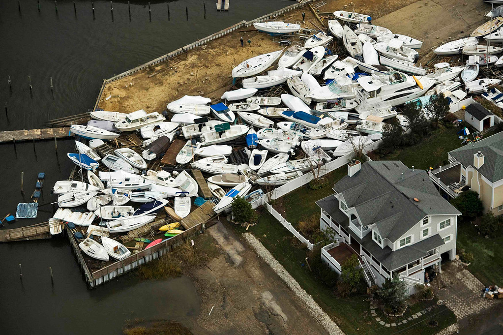 Description of . Boats are seen in a yard, where they washed onto shore during Hurricane Sandy, near Monmouth Beach, New Jersey October 31, 2012. The U.S. Northeast began an arduous slog back to normal on Wednesday after historic storm Sandy crippled transportation, knocked out power for millions and killed at least 64 people with a massive storm surge that caused epic flooding. REUTERS/Steve Nesius