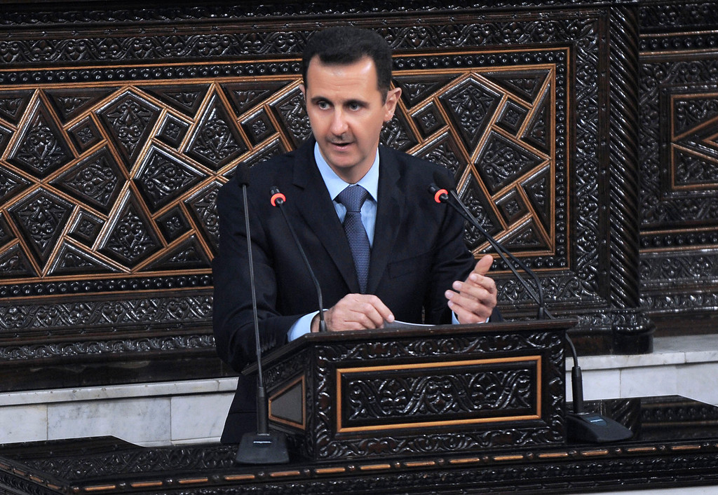 Description of . In this photo released by the Syrian official news agency SANA, Syrian President Bashar Assad addresses the nation during a speech at the Parliament in Damascus, Syria, Wednesday, March 30, 2011. Syria's president has blamed the wave of protests against his authoritarian rule on