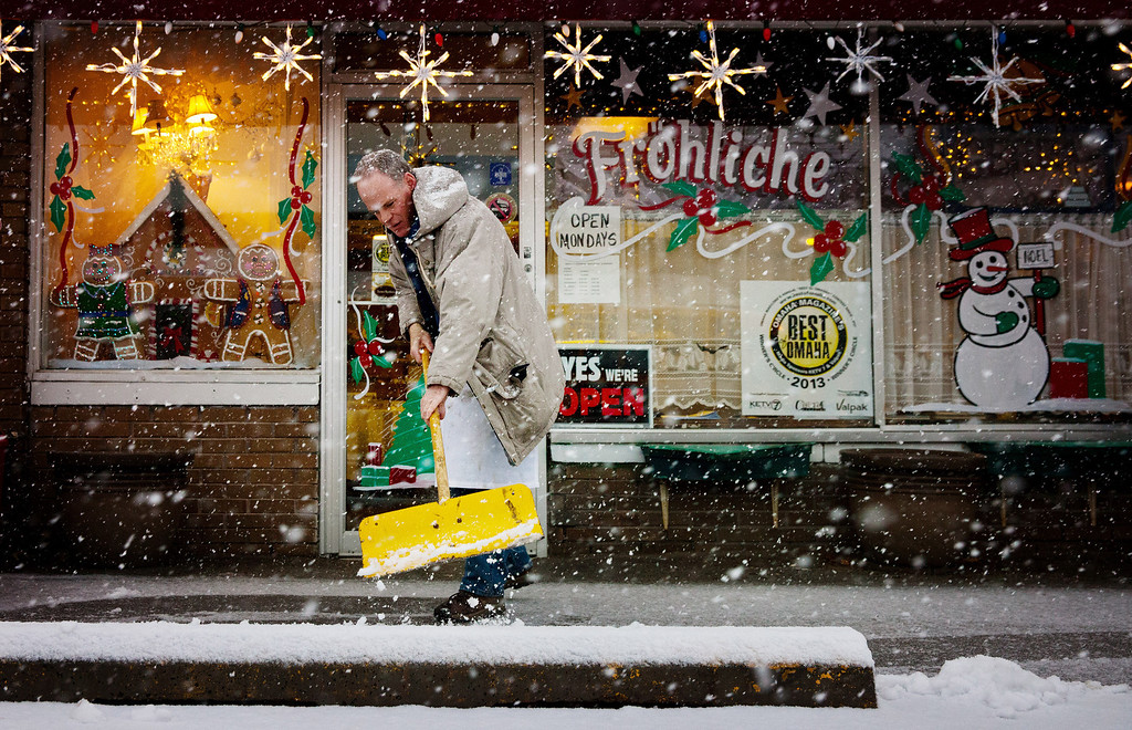 Description of . Don Hunter shovels outside of Gerda's German Restaurant and Bakery in Omaha Neb., Wednesday, Dec. 19, 2012. A storm that has dumped more than a foot of snow in the Rocky Mountains is heading east and is forecast to bring the first major winter storm of the season to the central plains and Midwest. (AP Photo/The World-Herald, Alyssa Schukar)