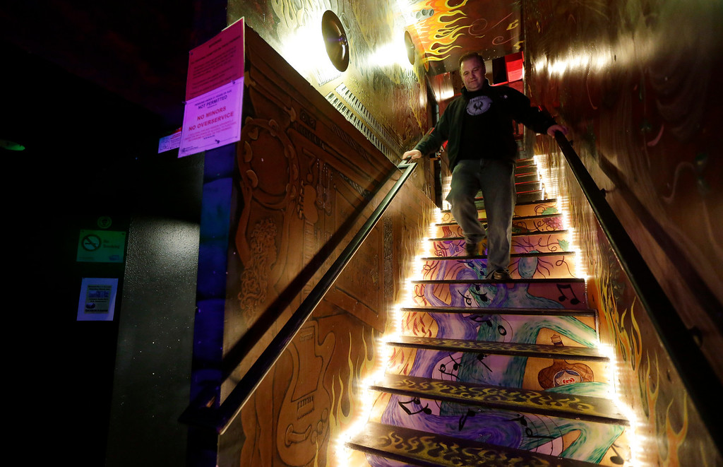 Description of . Jeff Call, owner of the Stonegate pizza-and-rum bar in Tacoma, Wash., walks Saturday, March 2, 2013, down the stairs that lead to the second-floor private club lounge area of the bar that allows the use of marijuana in the form of non-smoke vapor. Call charges patrons a small fee to become a member of the private second-floor club, which prohibits smoking marijuana, but does permit