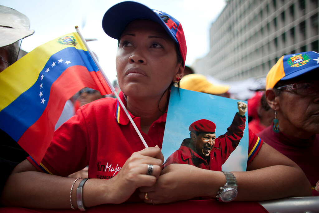 Description of . A woman holds a picture of Venezuela's President Hugo Chavez and the country's national flag during an event commemorating the violent street protests of 1989 known as the