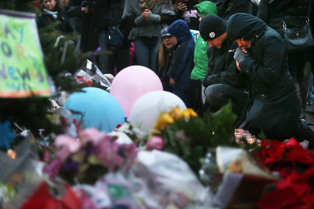Description of . NEWTOWN, CT - DECEMBER 16:  People gather at a memorial for victims near the school on the first Sunday following the mass shooting at Sandy Hook Elementary School on December 16, 2012 in Newtown, Connecticut. U.S. President Barack Obama visited the grief stricken town today.  (Photo by Mario Tama/Getty Images)