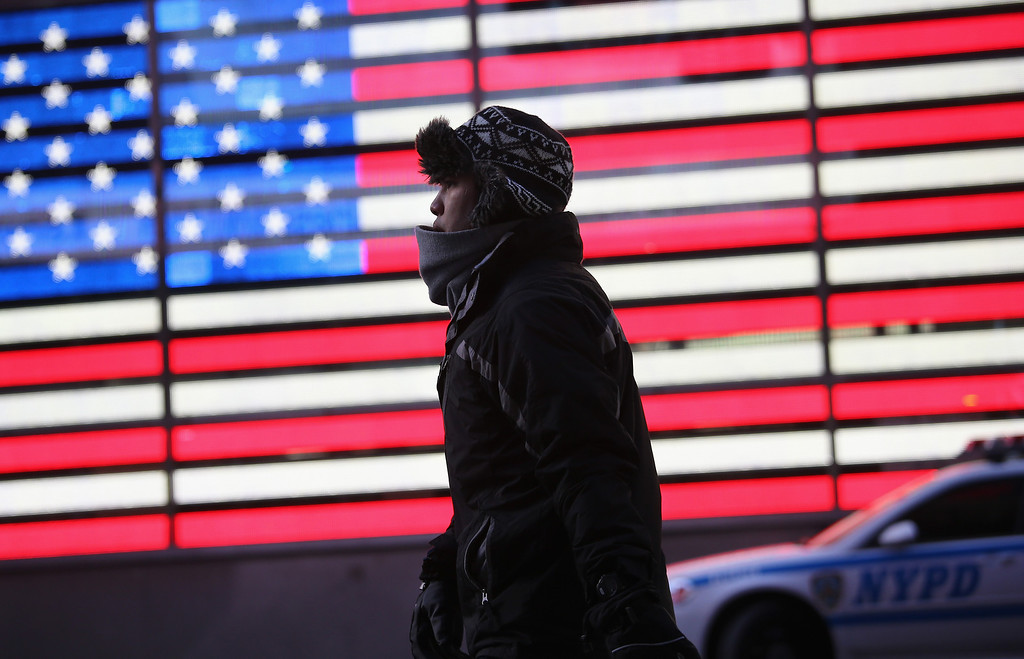 Description of . A man walks past an American flag sign in the cold through Times Square in Midtown Manhattan on January 7, 2014 in New York City.  A 'polar vortex' of frigid air centered on the North Pole dropped temperatures to a record low 4 degrees in New York City.  (Photo by John Moore/Getty Images)