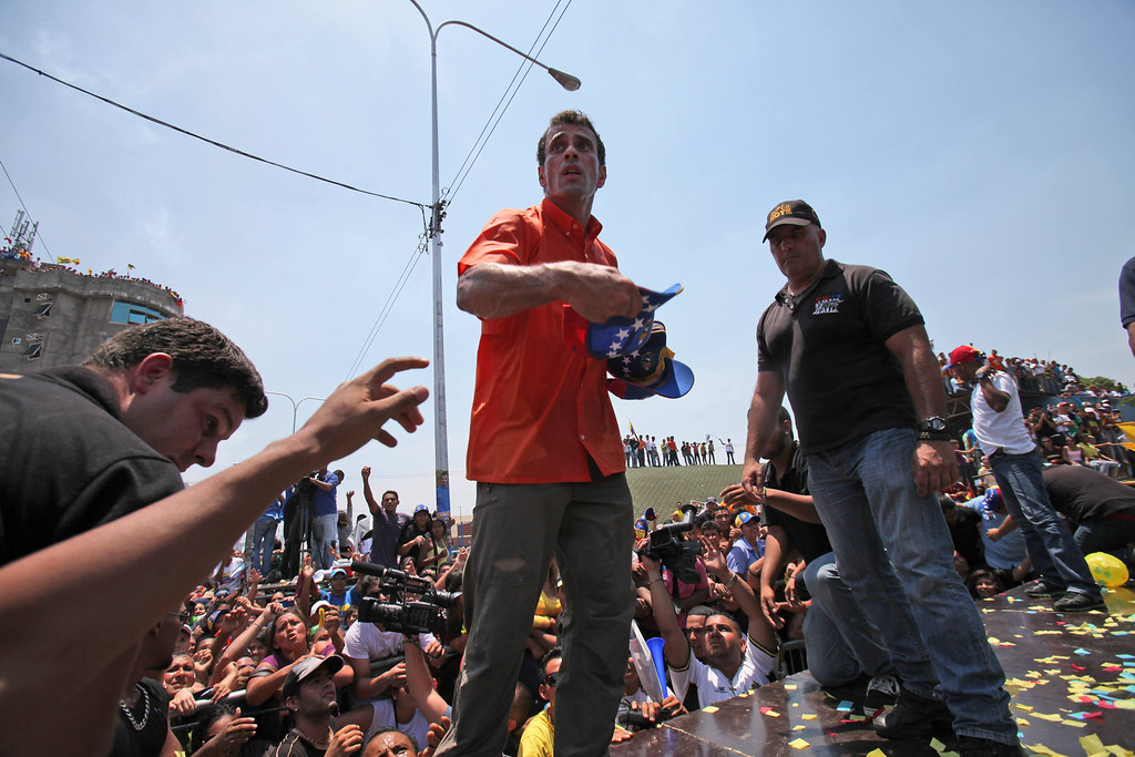 Description of . Opposition presidential candidate Henrique Capriles throws out baseball caps to supporters at a campaign rally in San Fernando de Apure, Venezuela, Thursday, April 11, 2013. Capriles is running against the ruling party candidate Nicolas Maduro in the upcoming April 14 presidential election. (AP Photo/Fernando Llano)
