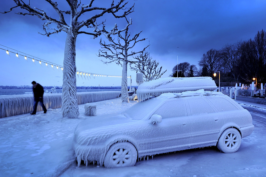 . A man walks past an ice covered car on the frozen waterside promenade at Lake Geneva in the city Versoix, near Geneva on early February 5, 2012. The death toll from the vicious cold snap across Europe has risen to more than 260, with the winter misery set to hit thousands of those seeking to escape it as air traffic was hit. (FABRICE COFFRINI/AFP/Getty Images)