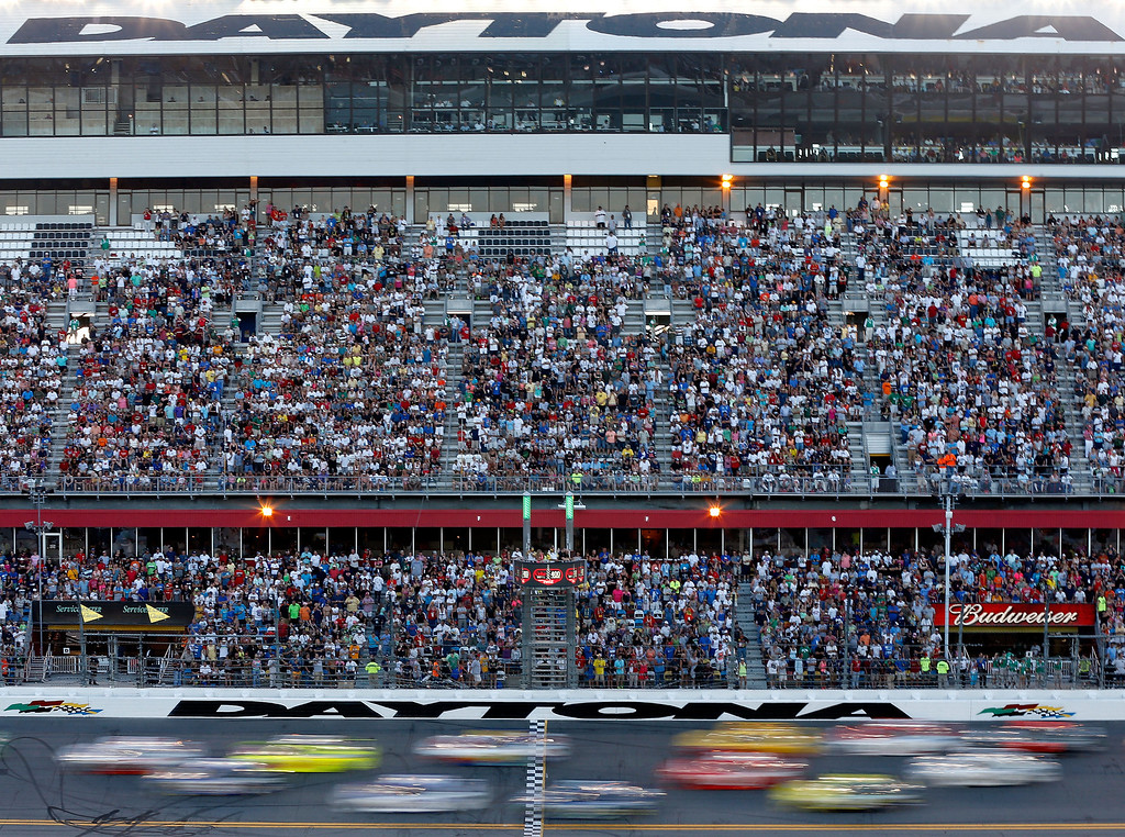 Description of . DAYTONA BEACH, FL - JULY 06:  Cars race down the frontstretch past the gransstand during the NASCAR Sprint Cup Series Coke Zero 400 at Daytona International Speedway on July 6, 2013 in Daytona Beach, Florida.  (Photo by Scott Halleran/Getty Images)