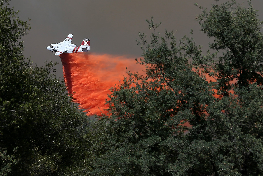 Description of . GROVELAND, CA - AUGUST 22:  A California Department of Forestry air tanker drops fire retardant on a ridge ahead of the advancing Rim Fire on August 22, 2013 in Groveland, California. The Rim Fire continues to burn out of control and threatens 2,500 homes outside of Yosemite National Park. Over 1,000 firefighters are battling the blaze that was reduced to only 2 percent containment after it nearly tripled in size overnight.  (Photo by Justin Sullivan/Getty Images)