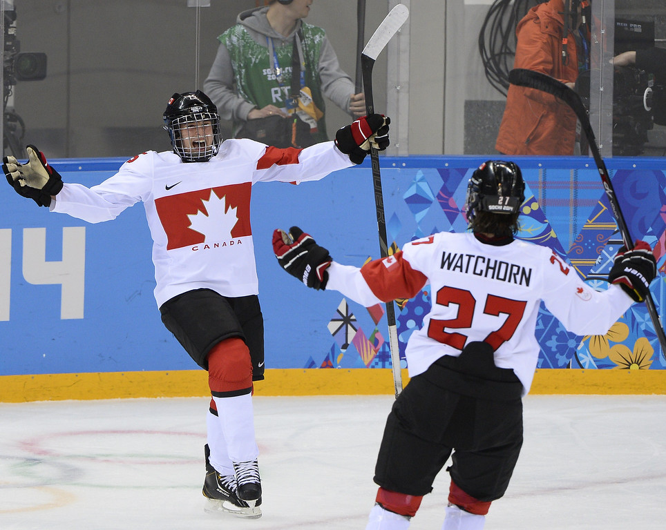 Description of . Melodie Daoust (L) celebrates with teammate Canada's Tara Watchorn (R) during the Women's Ice Hockey Play-offs Semifinals match Canada vs Switzerland at the Shayba Arena during the Sochi Winter Olympics on February 17, 2014.   JONATHAN NACKSTRAND/AFP/Getty Images