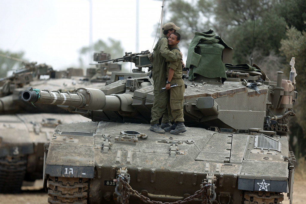 Description of . Israeli soldiers hug as they stand on a Merkava tank, at an army deployment area near Israel's border with the Gaza Strip, on July 17, 2014. Israel and the Islamist Hamas movement have agreed on a ceasefire that will begin at 0300 GMT on Friday, an Israeli official told AFP. AFP PHOTO /MENAHEM KAHANA/AFP/Getty Images