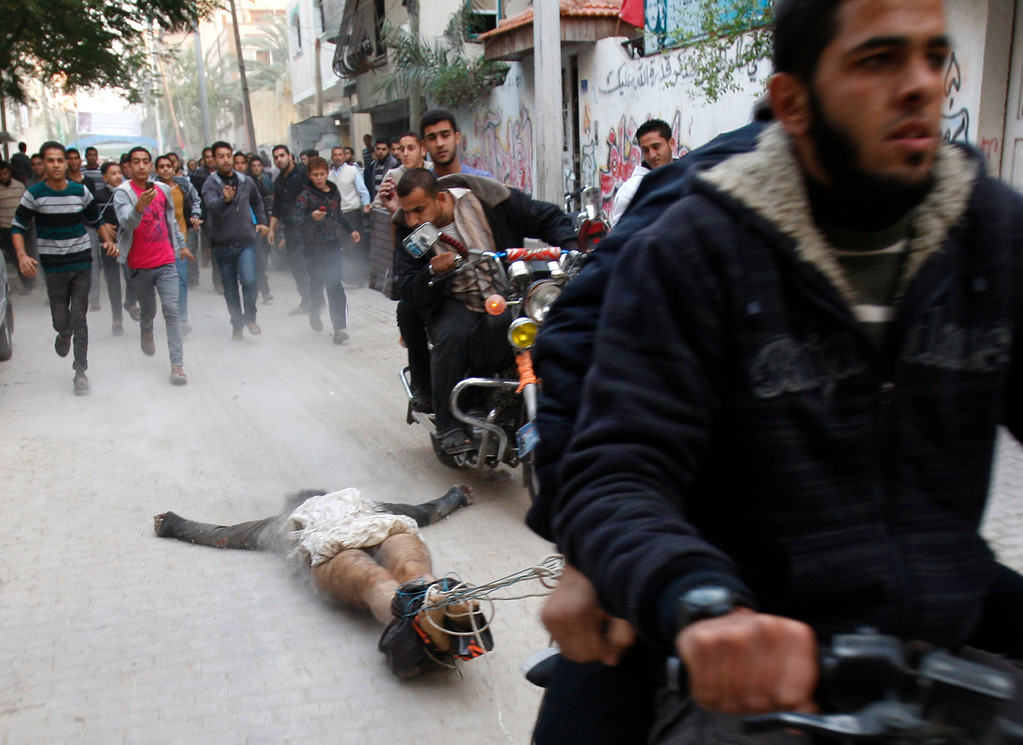 Description of . In this Nov. 20, 2012 file photo, Palestinian gunmen ride motorcycles as they drag the body of a man who was killed earlier as a suspected collaborator with Israel, in Gaza City. This photo by Associated Press photographer Adel Hana won the third place prize for the Spot News singles category in the World Press Photo 2013 photo contest.(AP Photo/Adel Hana, File)