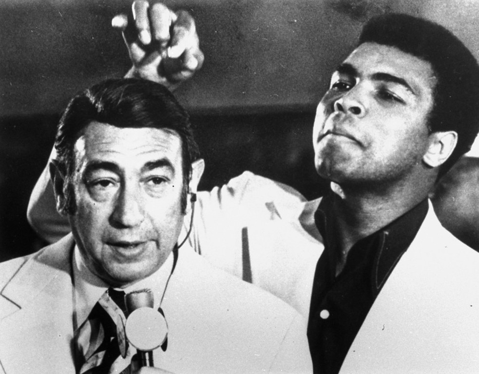 Description of . Muhammad Ali, former world heavyweight boxing champion, toys with the finely combed hair of television sports commentator Howard Cosell before the start of the Olympic boxing trials, August 7, 1972, in West Point, N.Y.  (AP Photo/Joe Caneva)