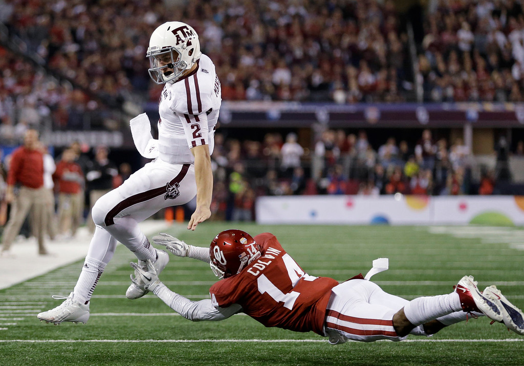 Description of . Texas A&M quarterback Johnny Manziel is run out of bounds by Oklahoma 's Aaron Colvin (14) during the second half of the Cotton Bowl NCAA college football game Friday, Jan. 4, 2013, in Arlington, Texas. (AP Photo/LM Otero)