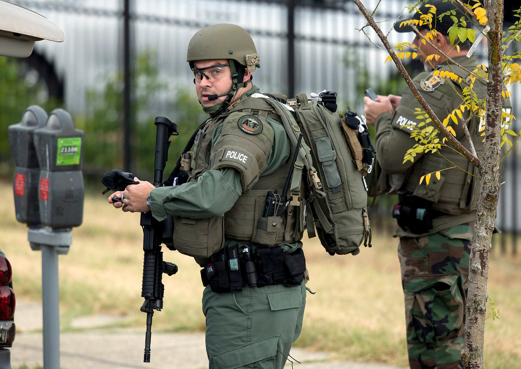 . Armed police prepare to enter the Washington Navy Yard as they respond to a shooting in Washington, Monday, Sept. 16, 2013. At least one gunman opened fire inside a building at the Navy yard. (AP Photo/Manuel Balce Ceneta)
