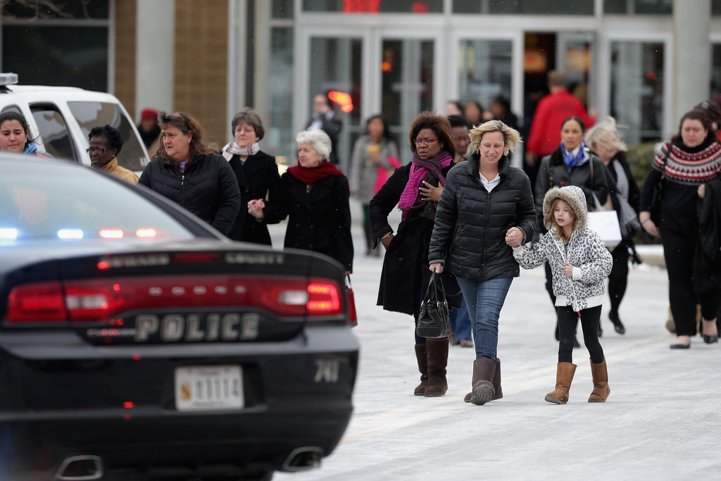 Description of . Police evacuate employees and patrons from the Columbia Town Center Mall after three people were killed in a shooting there January 25, 2014 in Columbia, Maryland. Police still do not have a motive for the shooting but believe the shooter has been killed.  (Photo by Chip Somodevilla/Getty Images)