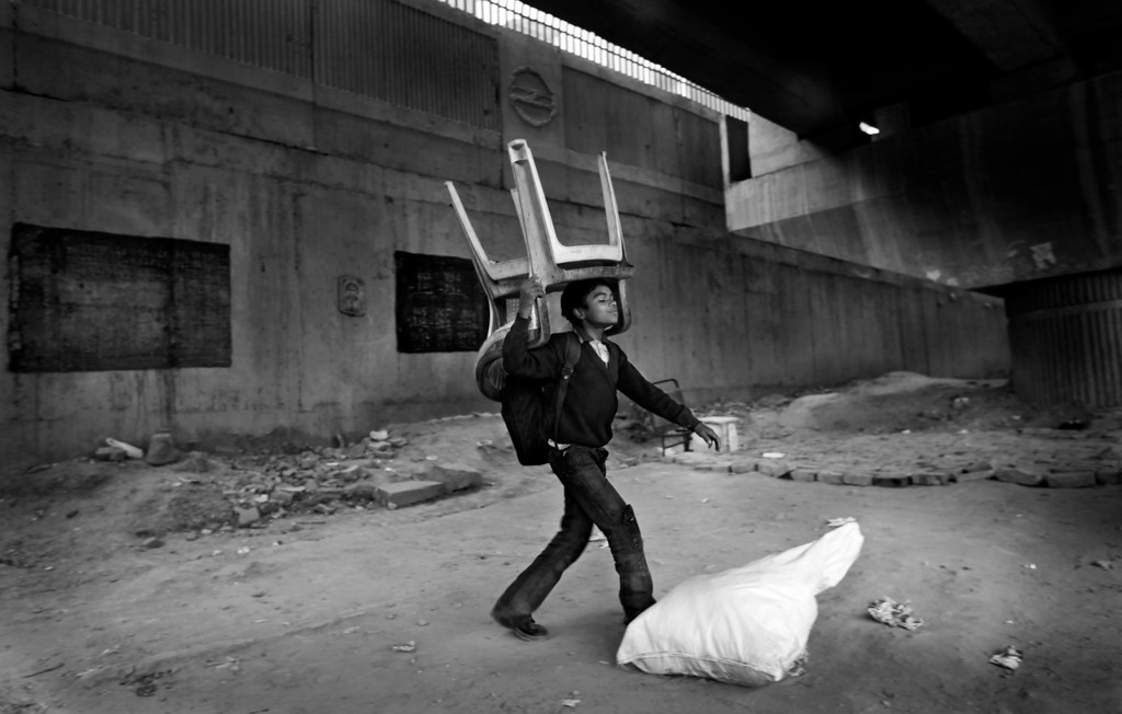 Description of . In this Dec. 11, 2012 photo, an underprivileged Indian boy tries to lift a sack containing mats while carrying plastic chairs on his head to store them till next morning at a temporary storeroom as class ends at a free school run under a metro bridge in New Delhi, India. This photo was one in a series of images by Associated Press photographer Altaf Qadri that received an honorable mention in the World Press Photo 2013 photo contest for the Contemporary Issues series category. (AP Photo/Altaf Qadri, File)